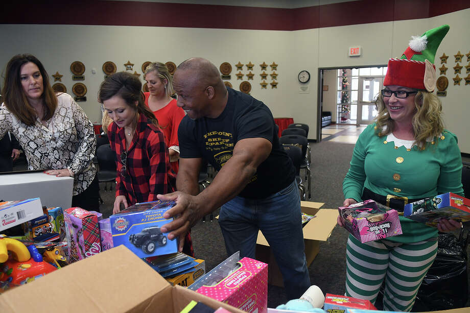 Sheriff Kenny Cotton, center, of the Pike County Sheriff's Dept. in Summit, MS., helps unpack bags of Christmas toys that he delivered to the Huffman ISD Administration Building with Monica Dorcz, from left, Grace Smith, and Melissa Hutchinson, from right, Principal at Ben Bowen Early Childhood Center, on Dec. 20, 2017. (Photo by Jerry Baker/Freelance) Photo: Jerry Baker, Freelance / Freelance