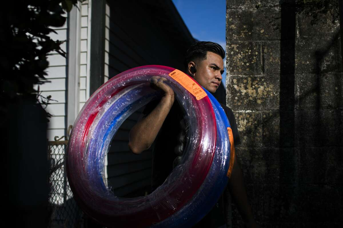 William Gilberto Landaverde, 22, a plumber from El Salvador living in New Orleans carries a box of plumbing supplies, in New Orleans.