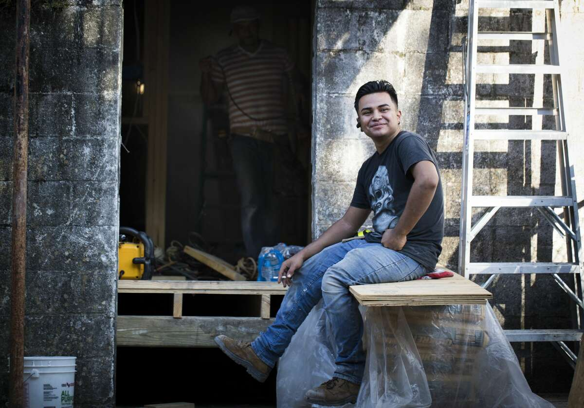 William Gilberto Landaverde, 22, takes a cigarette break at the renovation site of an apartment building in New Orleans.