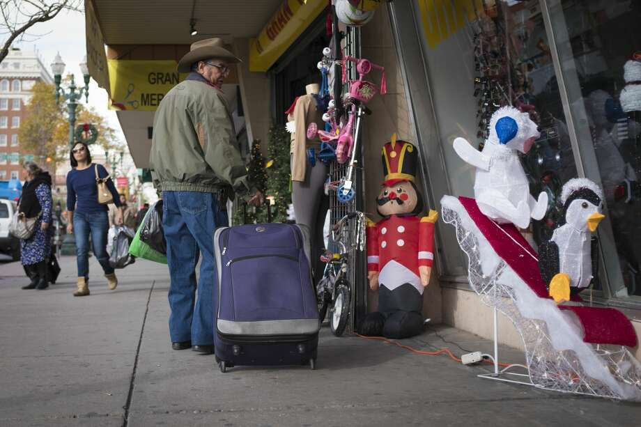 A commuter who has just entered El Paso from Ciudad Juarez, makes a stop to look at Christmas decorations while he carries his suitcase. Photo: Marie D. De Jesus/Houston Chronicle