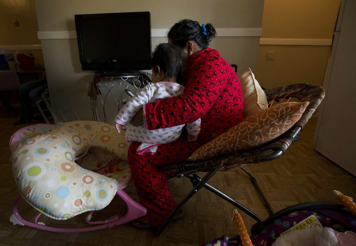 Lorena, 26, holds her four-month-old daughter after feeding her in Northwest Houston.