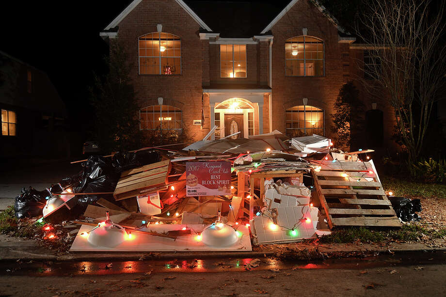 The Kalman home on Apple Forest Court sits behind a debris pile, courtesy of Hurricane Harvey, that the family decorated with Christmas lights and won the 2017 Kingwood Civic Club Best Block Spirit.