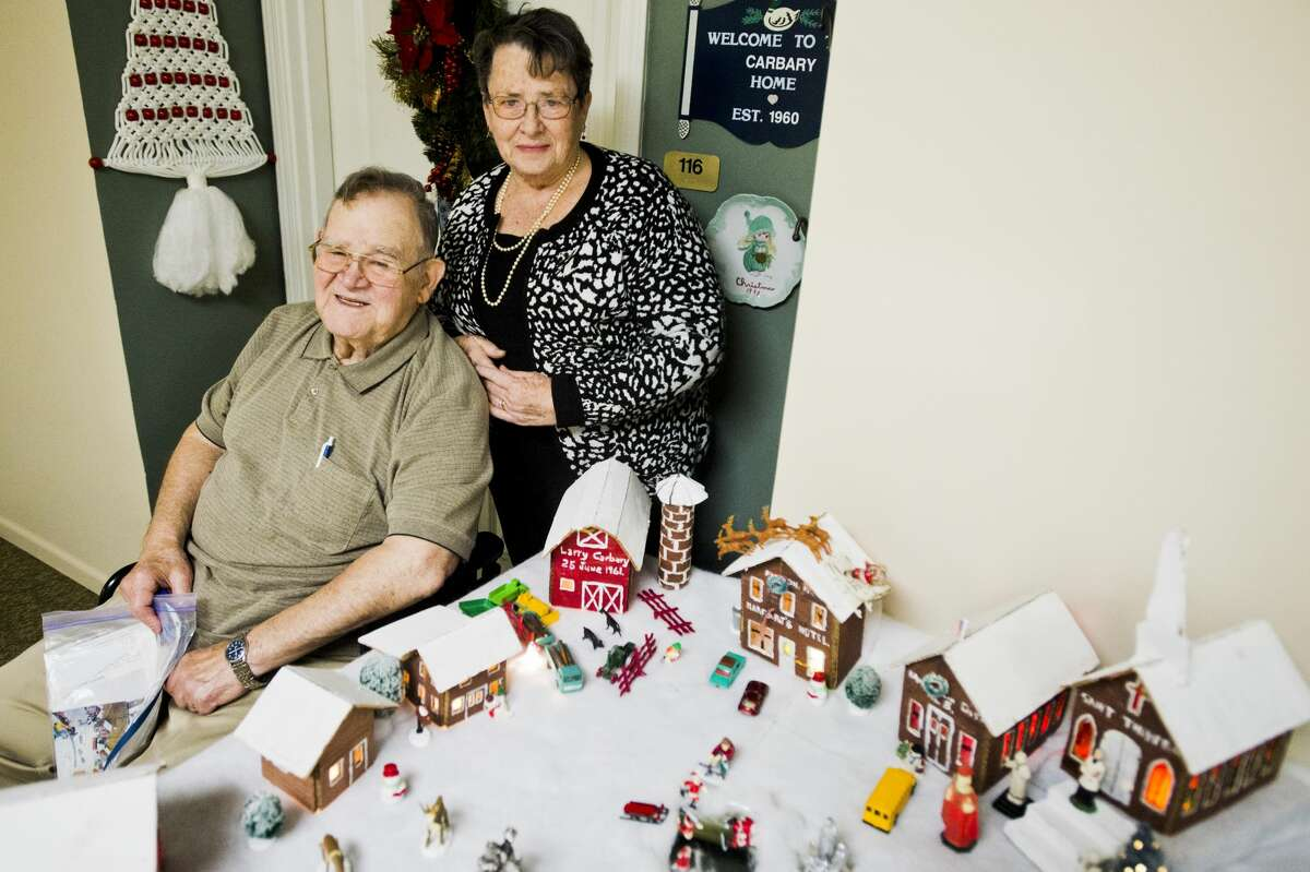 James and Nancy Carbary pose for a portrait with the cardboard village of Kawkawlin they built with their children in 1965 during their time in Taiwan. (Katy Kildee/kkildee@mdn.net)
