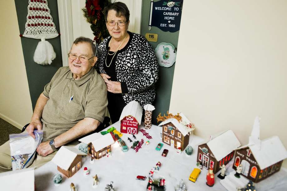 James and Nancy Carbary pose for a portrait with the cardboard village of Kawkawlin they built with their children in 1965 during their time in Taiwan. (Katy Kildee/kkildee@mdn.net) Photo: (Katy Kildee/kkildee@mdn.net)