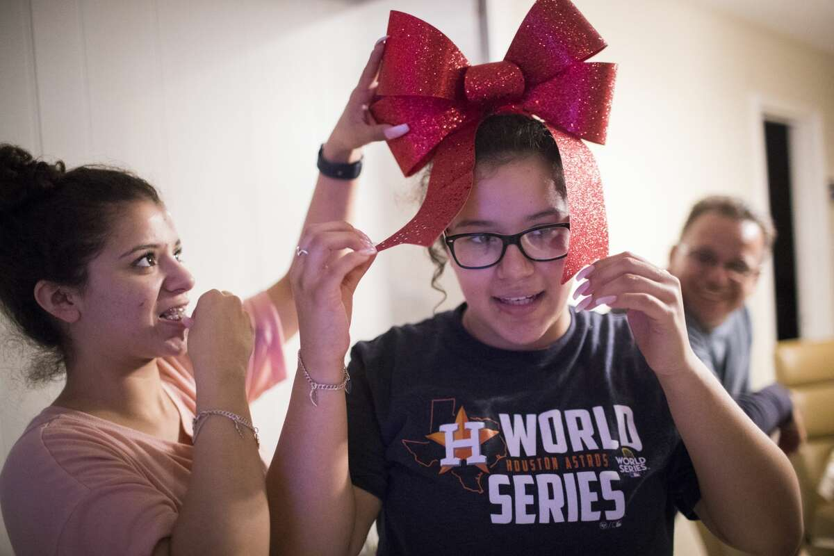 Karen, Rodriguez, left, puts a Christmas ornament on her sister Rebecca Rodriguez's head with a bobby pi, while their father Juan Rodriguez enjoys the scene from the back.