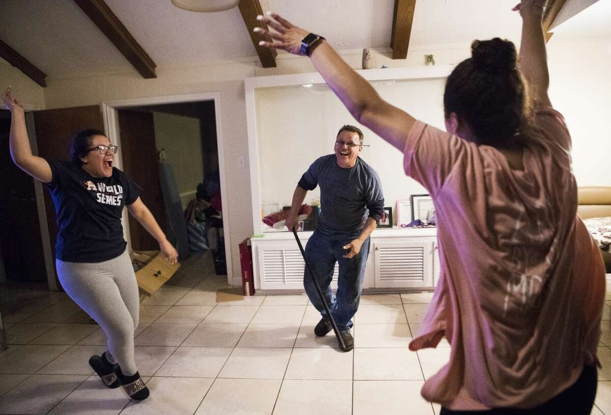 Rebecca Rodriguez, 16, Juan Rodriguez and Karen Rodriguez, 19, play games at their home in Houston.