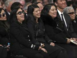 Mayor Ed Lee's wife, Anita Lee, and daughters, Brianna, middle, and Tania, laugh as former San Francisco Mayor Willie Brown reminisces about Lee during a service celebrating the life of Mayor Ed Lee at San Francisco City Hall in San Francisco, Sunday, Dec. 17, 2017. San Francisco Mayor Ed Lee was remembered for his humility, integrity and infectious smile during a public celebration of his life Sunday at City Hall attended by family members, former staff, politicians and residents.  (Scott Strazzante/San Francisco Chronicle via AP, Pool)