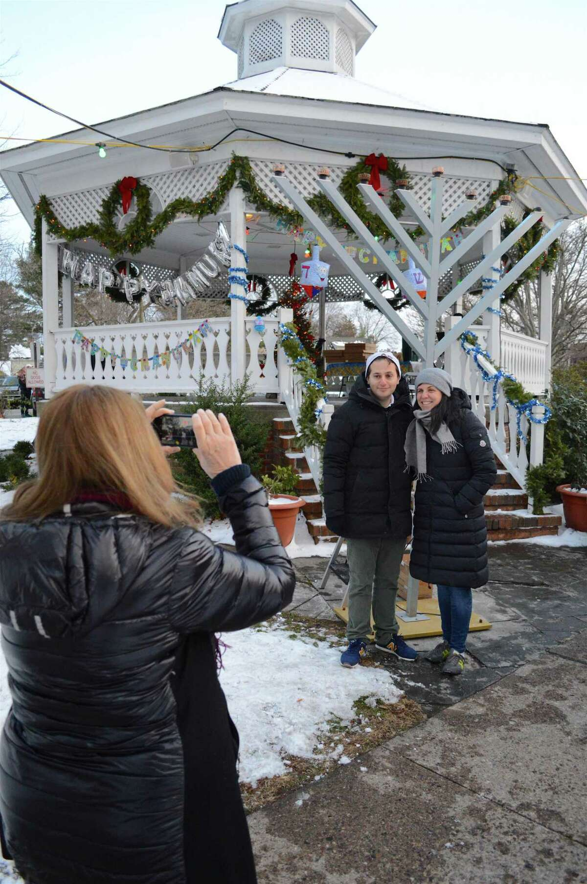 Vivian Shahrabani, of Westport, gets a shot of her friends Jonathan and Jacqueline Simon of New York City at the Hanukkah menorah lighting on Sherman Green, organized by Chabad of Fairfield, Sunday, Dec. 17, 2017, in Fairfield, Conn.