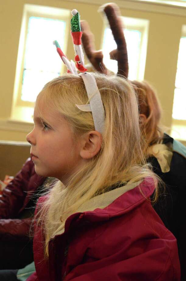 Maggie Martin, 4, of Darien, listens to holiday music at the Free Family Concert at the Seabury Center, sponsored by the Westport Historical Society and Mary Ann Hall's Music for Children and Beyond, Sunday, Dec. 17, 2017, in Westport, Conn. Photo: Jarret Liotta / For Hearst Connecticut Media / Westport News Freelance