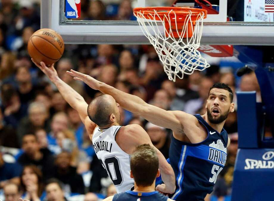Manu Ginobili is fouled going up for a shot by Dallas Mavericks' Salah Mejri of Tunisia in the second half of a Dec. 12, 2017 game in Dallas. The Mavericks won, 95-89. Photo: Tony Gutierrez /AP Photo
