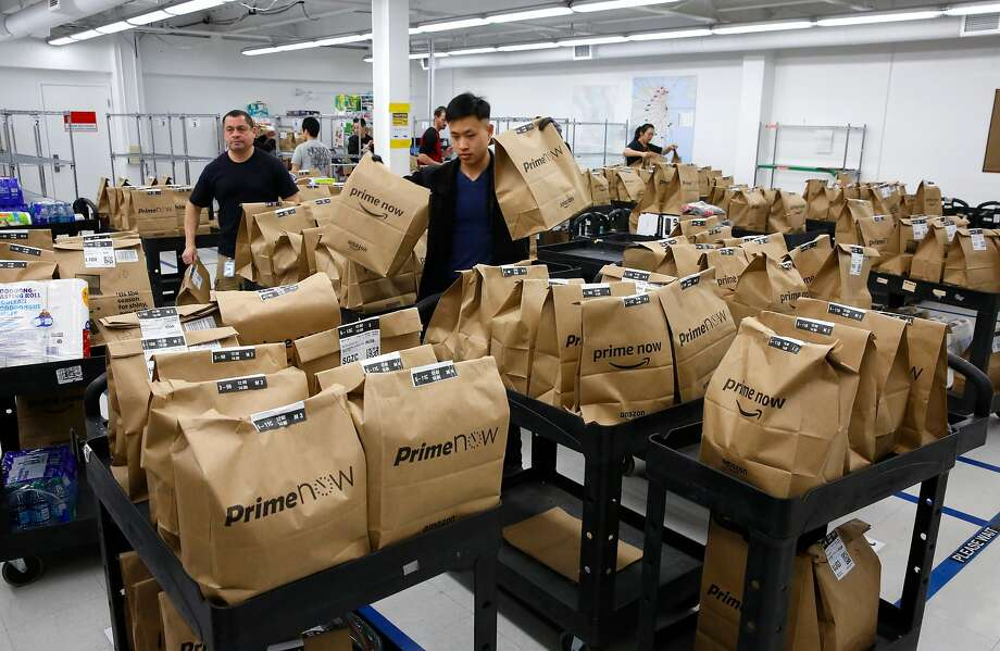 Amazon workers load carts with orders for Prime Now drivers at the company's San Francisco warehouse. Photo: Michael Macor, The Chronicle