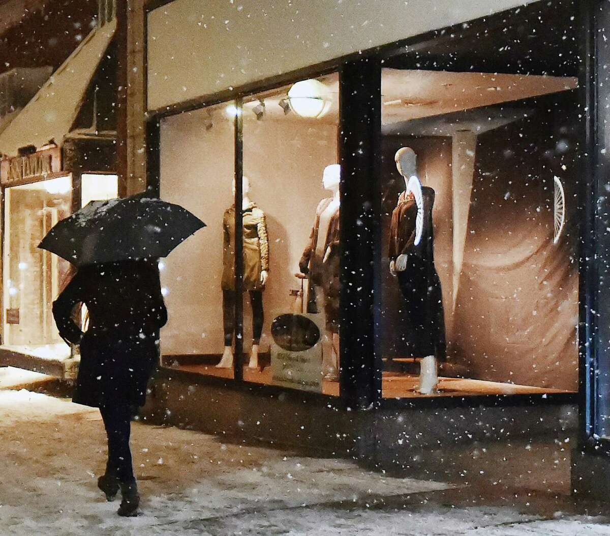 A mannequin in a window appears to be watching a woman walking with an umbrella on Chapel Street in New Haven during the snow storm, Saturday, Dec. 9, 2017. #ctweather
