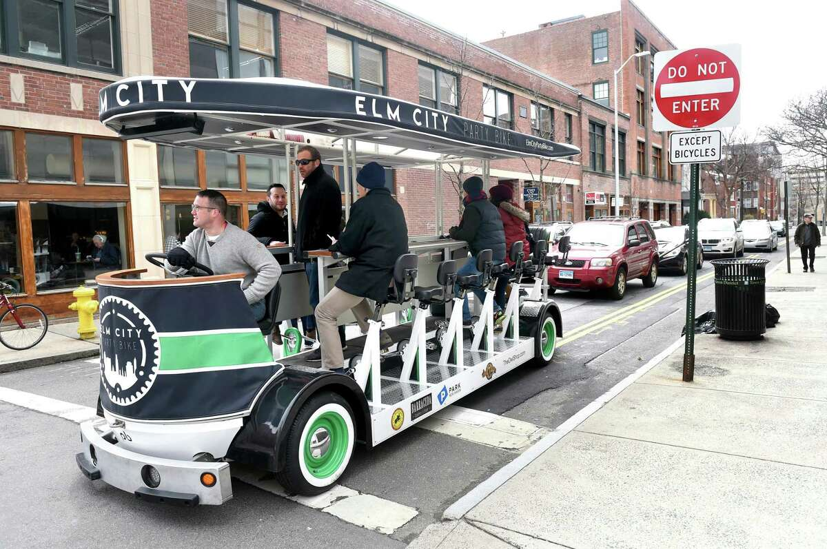 (Arnold Gold-New Haven Register) Elm City Party Bike co-owner Christian Bruckhart at the wheel of the party and sightseeing bike waits for the light to change at the corner of High and Chapel Street in New Haven on 4/1/2017. Standing behind him is co-owner Colin Caplan.
