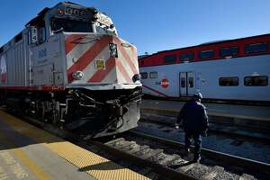 A CalTrain worker makes his way across the tracks in front of a train at the CalTrain Station in San Francisco, Calif., on Thursday December 21, 2017.