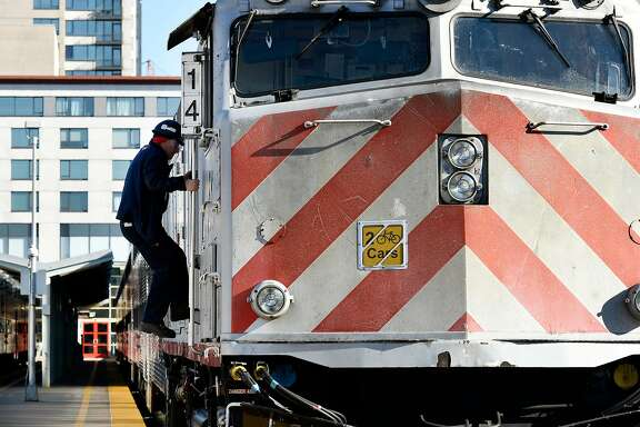 A worker climbs into an engine of a train as it sits at the CalTrain Station in San Francisco, Calif., on Thursday December 21, 2017.