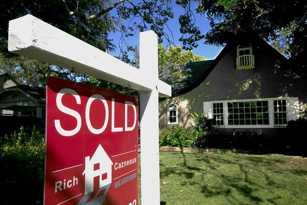 FILE - In this Wednesday, July 5, 2017, file photo, a sold sign is displayed in front of a house in Sacramento, Calif. On Thursday, Dec. 14, 2017, Mortgage buyer Freddie Mac said the benchmark 30-year home loan rate was down from 3.94 percent a week earlier and 4.16 percent a year ago. (AP Photo/Rich Pedroncelli, File)