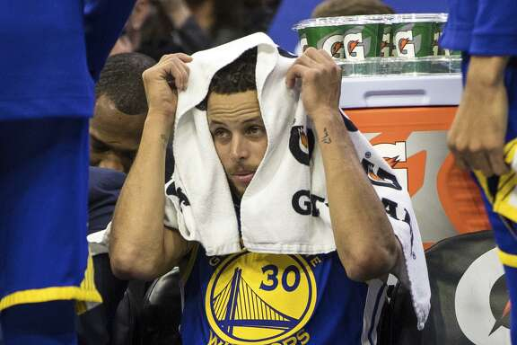 Golden State Warriors' Stephen Curry looks on from the bench during the first half of an NBA basketball game against the Philadelphia 76ers, Saturday, Nov. 18, 2017, in Philadelphia. The Warriors won 124-116. (AP Photo/Chris Szagola)