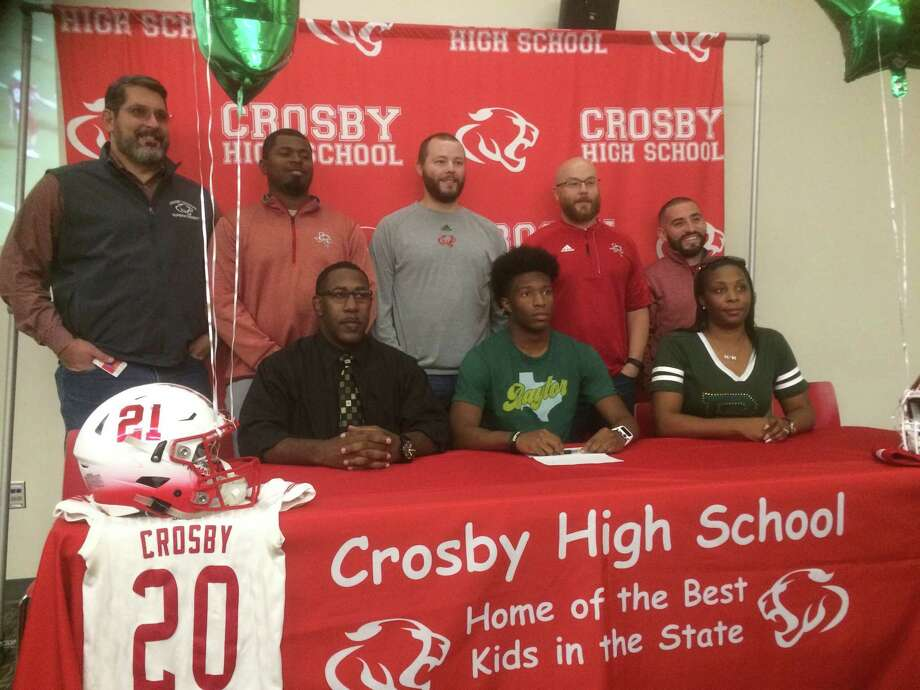 Crosby senior Craig Williams with his parents, coaches, and Crosby ISD superintendent Keith Moore at a celebration at Crosby High School on Dec. 21 for his signing his National Letter of Intent to play college football at Baylor University Photo: Elliott Lapin