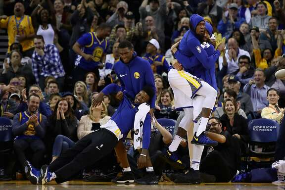 OAKLAND, CA - DECEMBER 20:  Jordan Bell #2, Kevon Looney #5, Kevin Durant #35 and JaVale McGee #1 of the Golden State Warriors celebrate after the Warriors made a basket against the Memphis Grizzlies at ORACLE Arena on December 20, 2017 in Oakland, California. NOTE TO USER: User expressly acknowledges and agrees that, by downloading and or using this photograph, User is consenting to the terms and conditions of the Getty Images License Agreement.  (Photo by Ezra Shaw/Getty Images)
