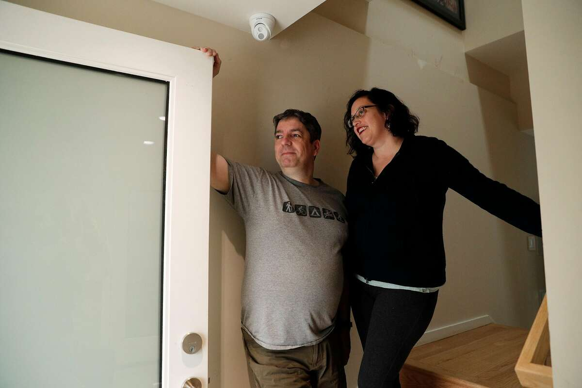 Alice Petty and Jason Hogg look out the front door of their home in San Francisco, Calif., on Tuesday, December 19, 2017. The couple installed a security video system in their Glen Park home, and recently capturing video of a porch pirate opening a package and stealing a keyboard they ordered online. The couple installed a Ring video doorbell, two other cameras, and a series of iPads inside so they can monitor the security video, which is stored on a local network storage drive.