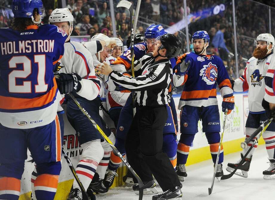 Linesman Kevin Briganti attempts to break up a fight between Springfield's Tony Turgeon and Bridgeport Sound Tiger Ross Johnston during the first period of their AHL hockey game at the Webster Bank Arena in Bridgeport, Conn. on Wednesday, April 4, 2017. Photo: Brian A. Pounds / Hearst Connecticut Media / Connecticut Post