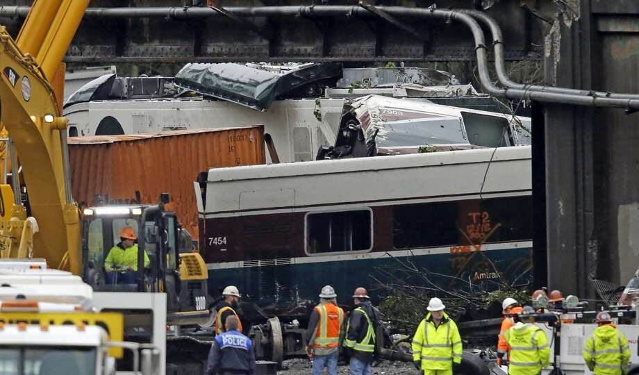 Train cars are jumbled together with vehicles below a railroad bridge at the scene of an Amtrak train crash onto Interstate 5 a day earlier Tuesday, Dec. 19, 2017, in DuPont, Wash. Federal investigators say they don't yet know why the Amtrak train was traveling 50 mph over the speed limit when it derailed Monday south of Seattle. (AP Photo/Elaine Thompson) Photo: Elaine Thompson / AP