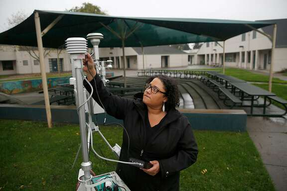 Air quality instrument specialist Ila Perkins uses instruments to check  particle levels in air at John B. Riebli Elementary School in Larkfield on Monday, November 20, 2017, in Santa Rosa, Calif.