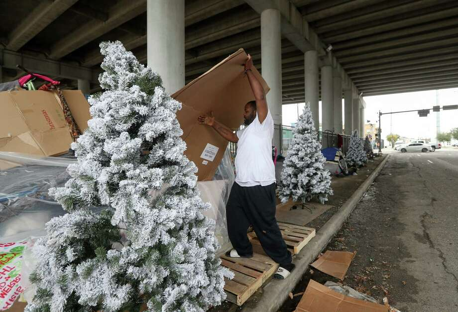 "Justin Jones looks for his friend, whose tent sits among several Christmas trees dropped off by a person along Congress Avenue, under IH-69, Thursday, Dec. 21, 2017, in Houston. ""Everyone has a wishlist, maybe a pack of cigarettes. It's Christmas,"" Jones said.  ( Jon Shapley / Houston Chronicle ) Photo: Jon Shapley, Staff Photographer / © 2017 Houston Chronicle"