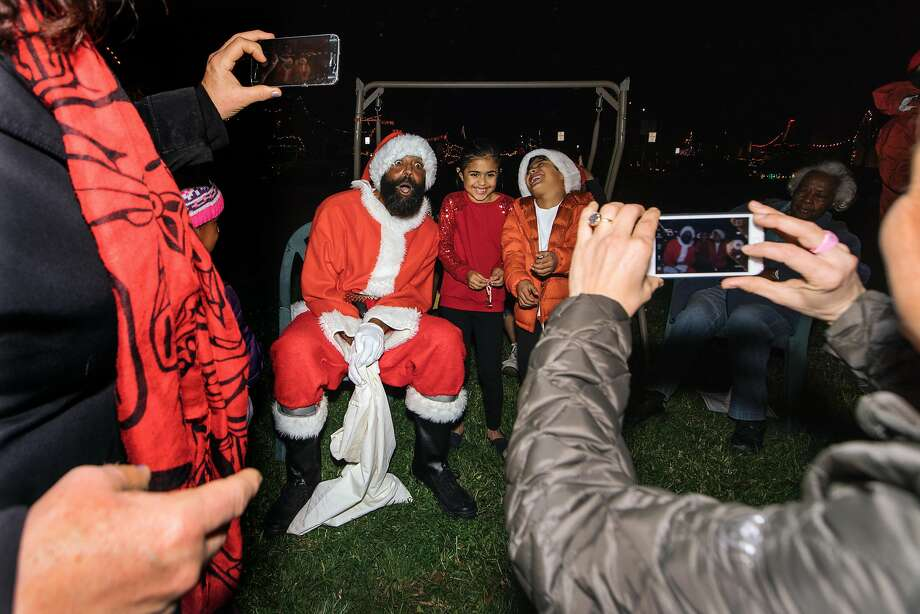 Neighbors attend the annual tree-lighting ceremony on Picardy Drive in Oakland. Photo: Peter Prato, Special To The Chronicle
