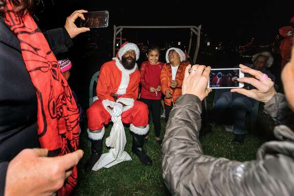Neighbors attend the tree lighting ceremony on Picardy Drive, in Oakland on December 9th, 2017. This particular block has a tradition of decorating and gathering for a tree lighting in the center island of the street that dates back to the mid-20th century. Gyasi Coles, 44, dressed as Santa Claus, moved in the neighborhood in 1977 from San Francisco. Coles agreed to dress up as Santa Clause because his father had done it once before.