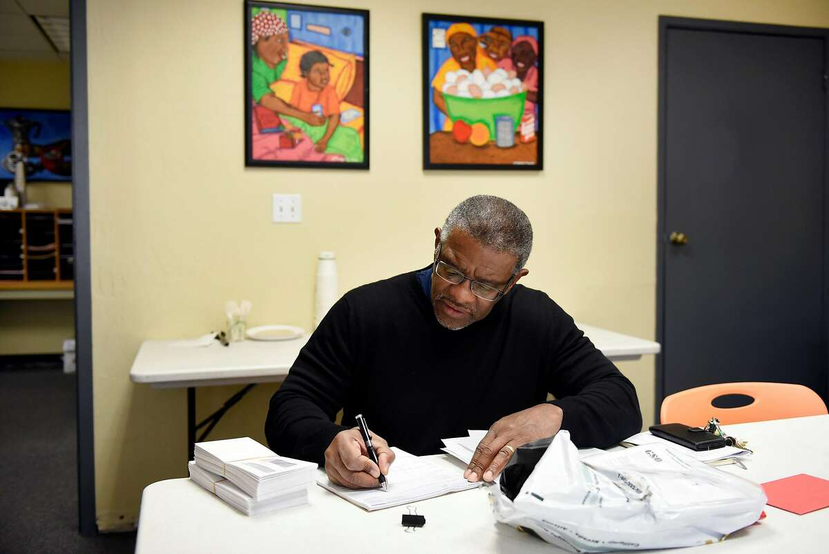Director Joe Wilson, signs payroll checks for his employees at the Hospitality House, a homeless outreach non-profit that recently celebrated it's 50th year of operation, in San Francisco, Calif., on Wednesday December 13, 2017.