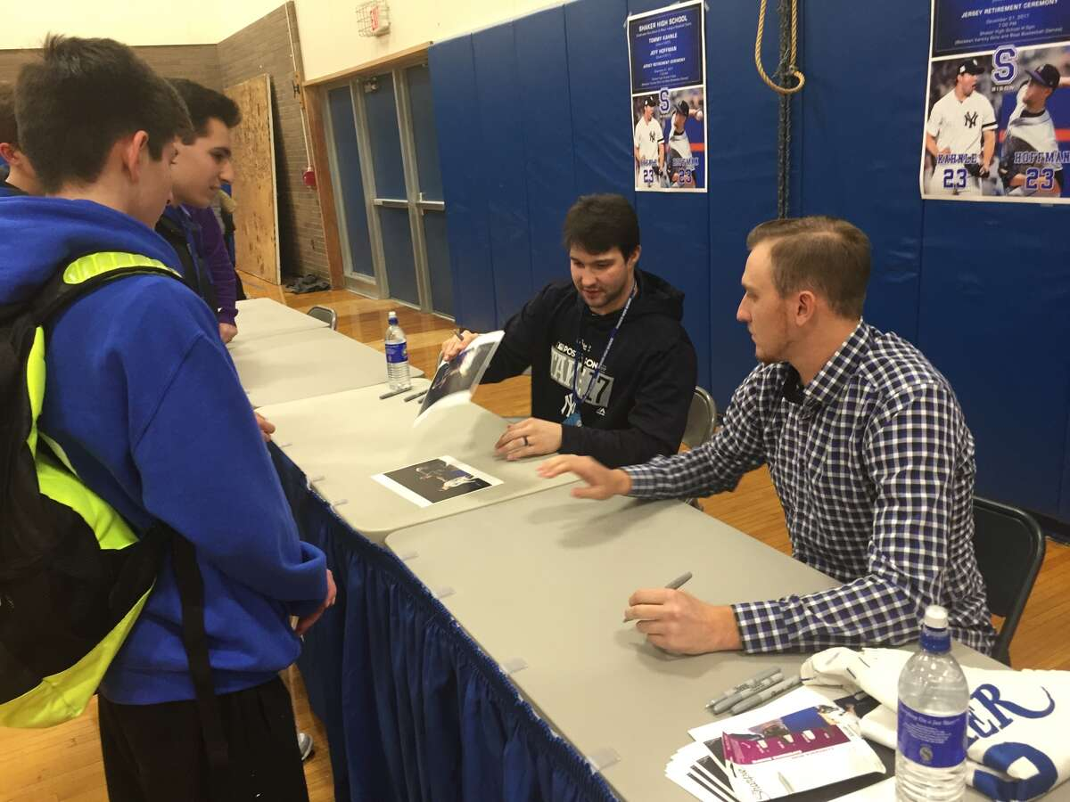 Shaker High School alums Tommy Kahnle, seated left, who pitches for the New York Yankees, and Jeff Hoffman, seated right, a pitcher for the Colorado Rockies, sign autographs at Shaker High School in Colonie on Dec. 20, 2017. (Leif Skodnick/Times Union)