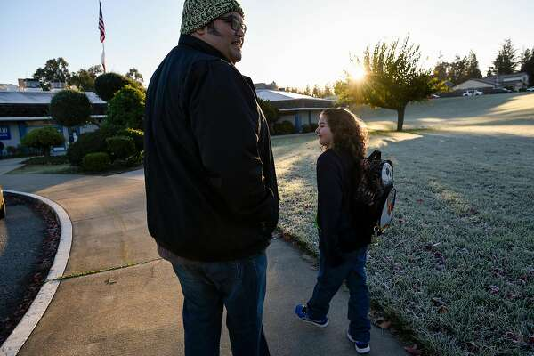 Ariel Juarez drops off his son Orion Juarez, 6, at his elementary school in San Jose, Calif., on Thursday December 21, 2017.