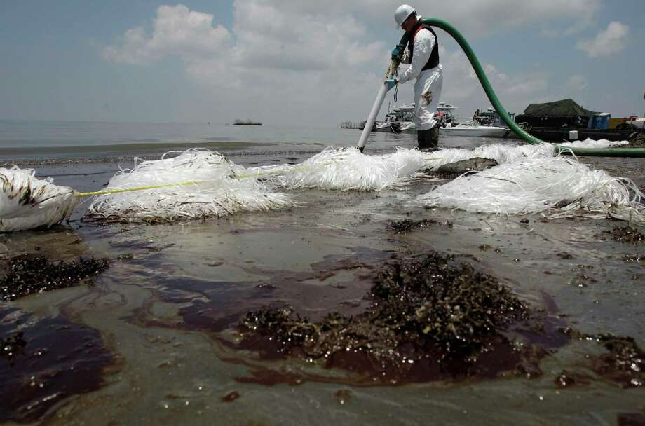 A worker in Belle Terre, La., uses a suction hose in mid-2010 to remove oil that washed ashore from the Deepwater Horizon spill. The Trump administration has stopped an independent study of offshore oil inspections by the agency created after the disaster. Photo: Eric Gay, STF / Copyright 2017 The Associated Press. All rights reserved.