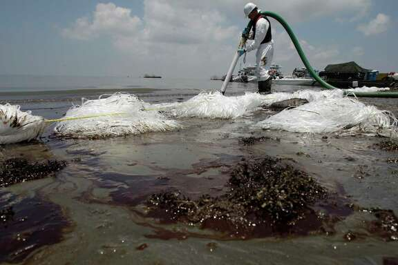 A worker in Belle Terre, La., uses a suction hose in mid-2010 to remove oil that washed ashore from the Deepwater Horizon spill. The Trump administration has stopped an independent study of offshore oil inspections by the agency created after the disaster.