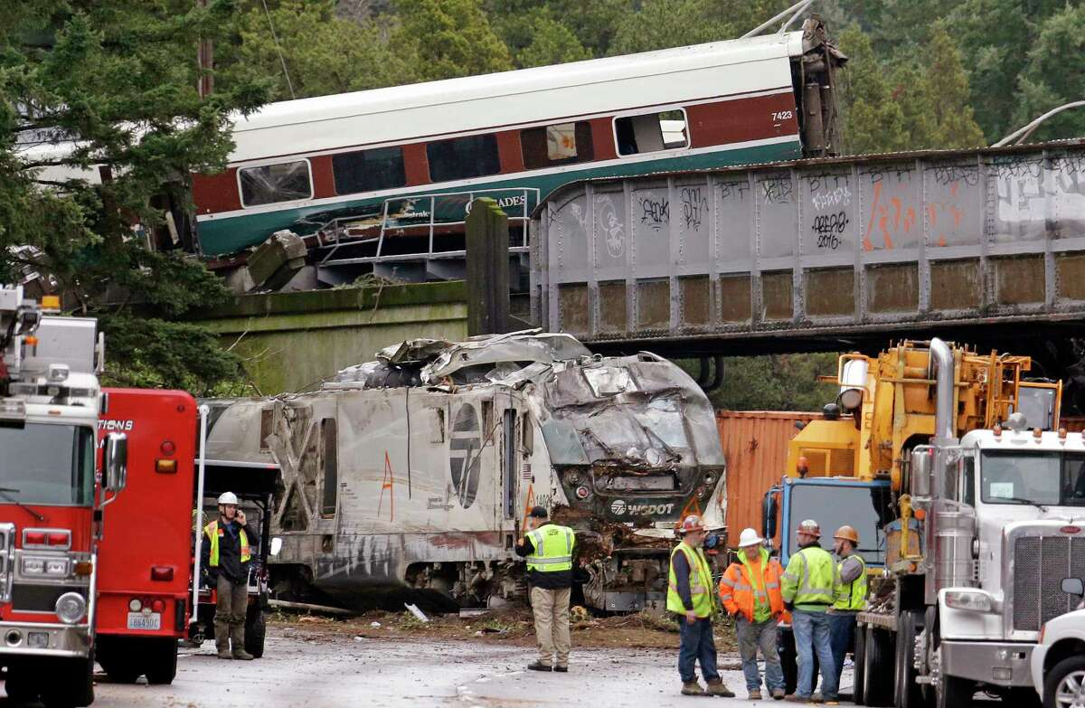 Cars from an Amtrak train lay spilled onto Interstate 5 below as some train cars remain on the tracks above Monday, Dec. 18, 2017, in DuPont, Wash. The Amtrak train making the first-ever run along a faster new route hurtled off the overpass Monday near Tacoma and spilled some of its cars onto the highway below, killing some people, authorities said. Seventy-eight passengers and five crew members were aboard when the train moving at more than 80 mph derailed about 40 miles south of Seattle before 8 a.m., Amtrak said. (AP Photo/Elaine Thompson) ORG XMIT: WAET105