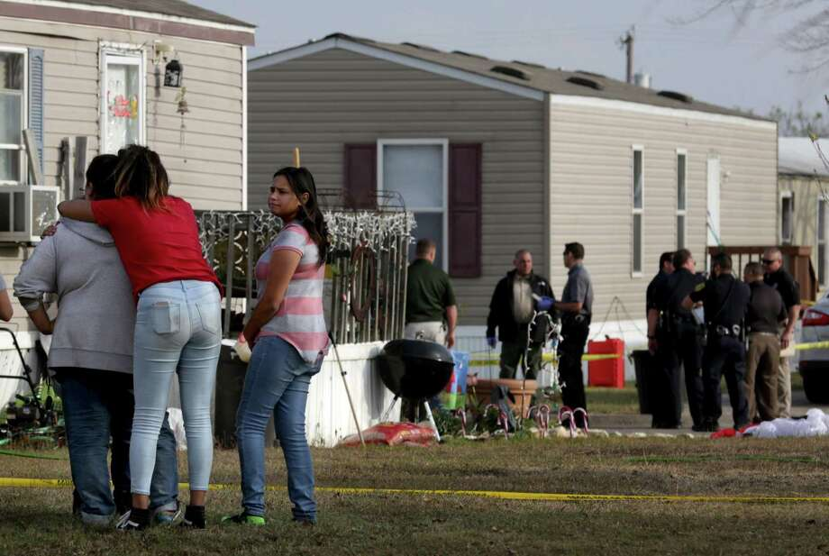 Residents of Pecan Grove Manufactured Home Community gather to watch Bexar County Deputies investigate near the scene of a deputy-involved shooting. A 7-year-old boy was fatally shot when Bexar County sheriff's deputies opened fire on a woman at a Schertz mobile home park after a lengthy manhunt Thursday. The woman — a wanted felon and a suspect in a car theft — also was killed by the gunfire. Photo: Bob Owen /San Antonio Express-News / San Antonio Express-News