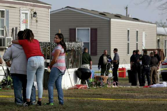 Residents of Pecan Grove Manufactured Home Community gather to watch Bexar County Deputies investigate near the scene of a deputy-involved shooting. A 7-year-old boy was fatally shot when Bexar County sheriff's deputies opened fire on a woman at a Schertz mobile home park after a lengthy manhunt Thursday. The woman — a wanted felon and a suspect in a car theft — also was killed by the gunfire.
