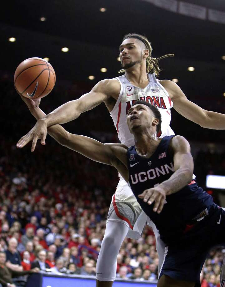 Arizona forward Keanu Pinder, top, fouls UConn's Jalen Adams during the first half Thursday. Photo: Rick Scuteri / Associated Press / FR157181 AP