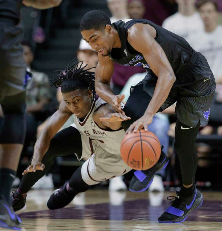 Texas A&M guard Jay Jay Chandler (0) dives for a loose ball against Buffalo guard CJ Massinburg (5) during the first half of an NCAA college basketball game Thursday, Dec. 21, 2017, in College Station, Texas. (AP Photo/Michael Wyke)