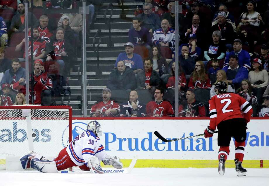 New Jersey Devils defenseman John Moore (2) scores a goal on New York Rangers goalie Henrik Lundqvist, of Sweden, during the first period of an NHL hockey game Thursday, Dec. 21, 2017, in Newark, N.J. (AP Photo/Julio Cortez) Photo: Julio Cortez / Copyright 2017 The Associated Press. All rights reserved.