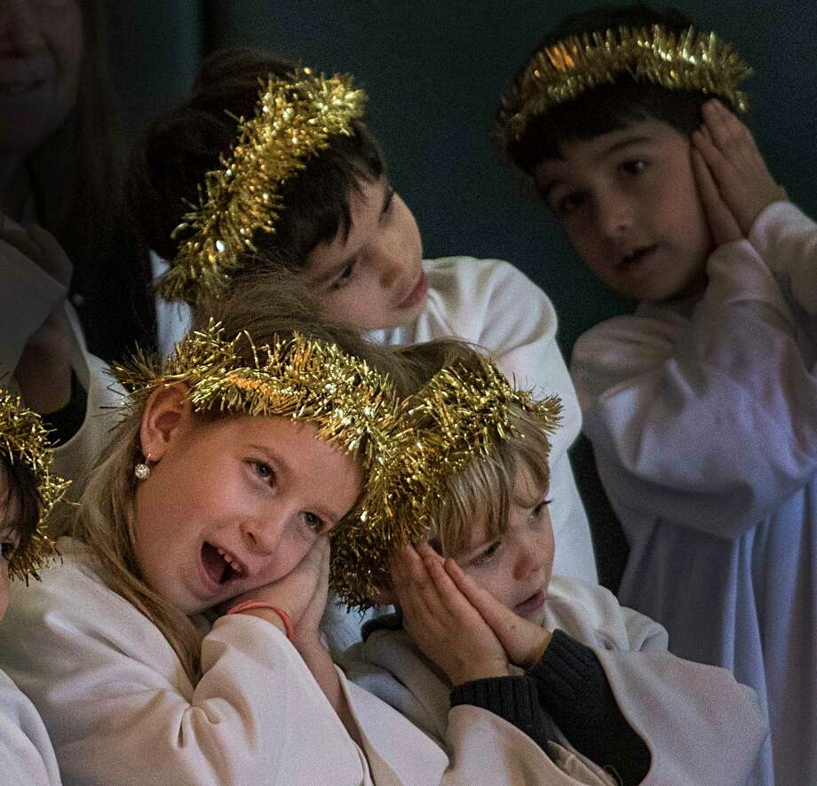 Angles made up of the school's kindergarten and first grade join the gathering at the manger set up and shown off for the assembly at the St. Shomas the Apostle School during their Christmas play Thursday Dec 21, 2017 in Bethlehem, N.Y.  (Skip Dickstein/ Times Union) Photo: SKIP DICKSTEIN / 20042485A