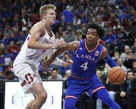 Kansas guard Devonte' Graham (4) drives to the basket around Stanford defender Michael Humphrey (10)) during the first half of an NCAA college basketball game in Sacramento, Calif., Thursday, Dec. 21, 2017. (AP Photo/Steve Yeater)