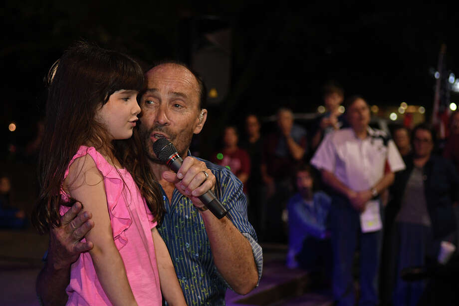 "Lee Greenwood performs ""God Bless the USA"" with help from Morgan Iler, 6, from Cypress and a 1st grader at Second Baptist School during his concert at Kingwood Town Center last Thursday night. Morgan's mom Meredith, a Rotarian, said that Morgan learned how to read from Greenwood's book with the same title as the song ""God Bless the USA"". Photo: Jerry Baker, Freelance / Freelance"