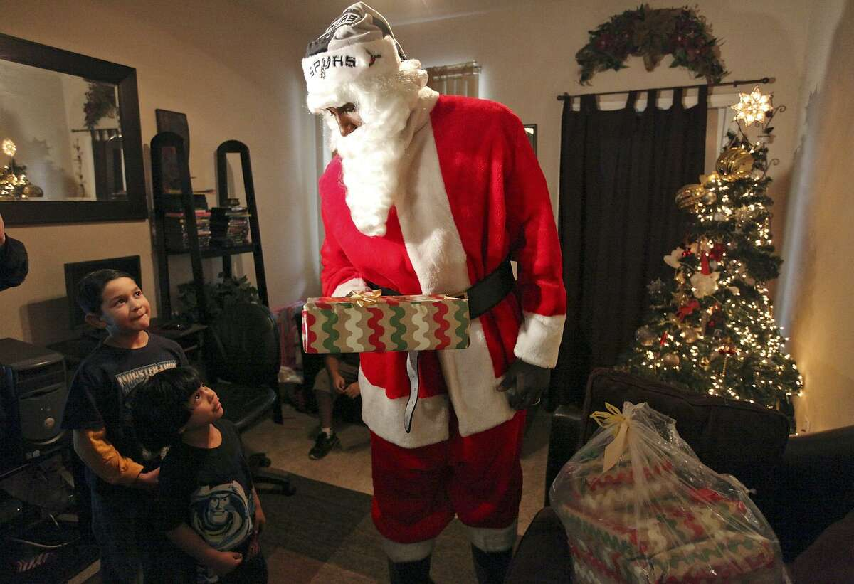Spurs' DeJuan Blair, dressed as Santa Claus, gives gifts to Robert Rodriguez, 7, (from left) and his brother Lorenzo Alcaraz, 5, Dec. 23, 2011, at their home in the Rosemont at Highland Park Apartments as part of the Elf Louise Christmas project.