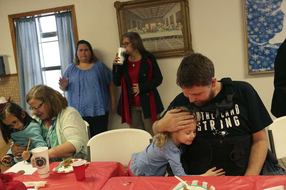 Kris Workman holds his daughter, Eevee Workman, 3, at the First Baptist Church Christmas Potluck in Sutherland Springs on Sunday, Dec. 17, 2017. Sunday was Workman's first visit back to the church since he was shot in the back and paralyzed from the waist down on Nov. 5. At left is Stormy Choate with Yazmeen Briggs, 5. Photo: SAN ANTONIO EXPRESS-NEWS / SAN ANTONIO EXPRESS-NEWS / SAN ANTONIO EXPRESS-NEWS