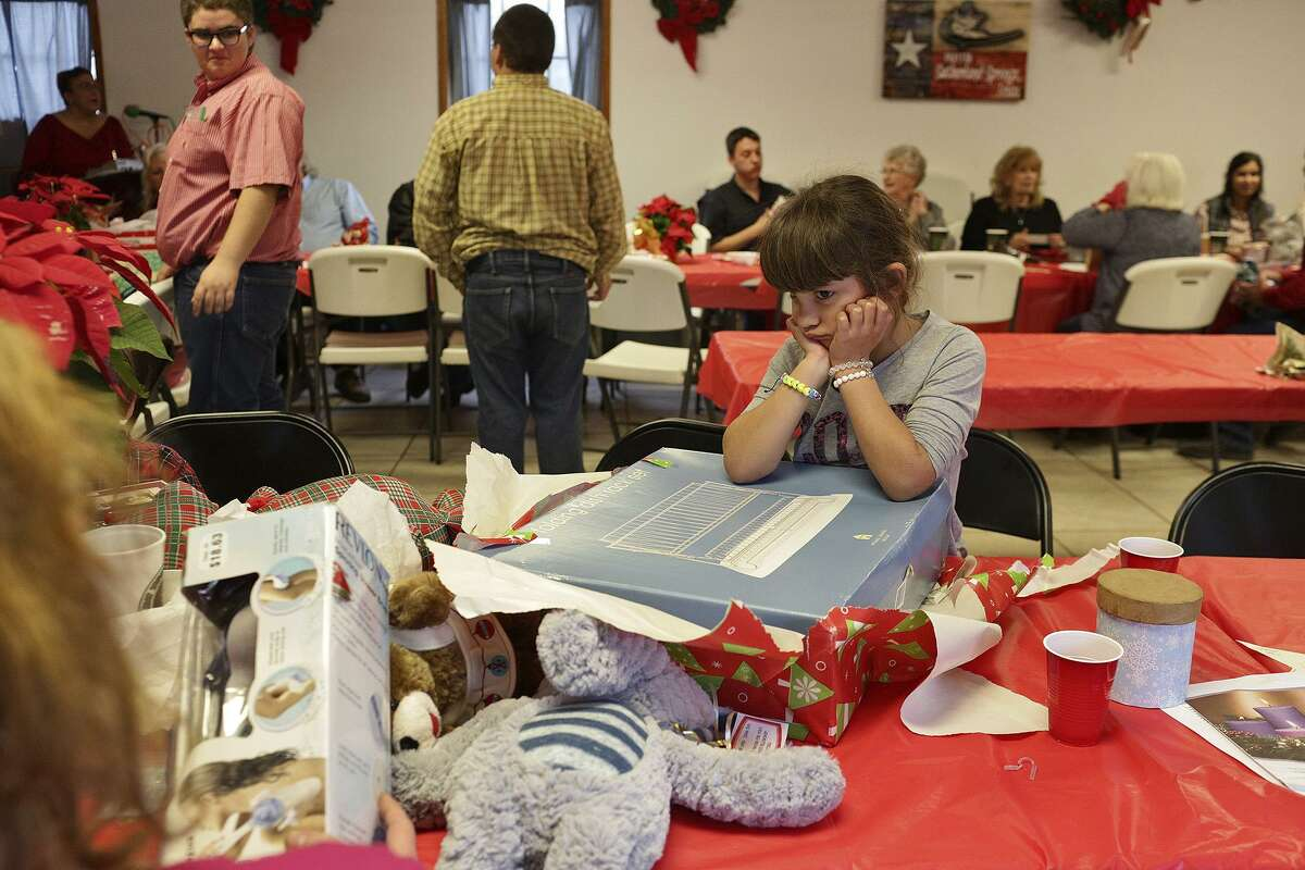Haley Ward, 7, pouts a bit after opening up her White Elephant gift, a dish drying rack, during the Christmas Potuck at First Baptist Church in Sutherland Springs on Dec. 17, 2017. Two of Ward's nieces were killed and her nephew, Ryland Ward, 5, was shot five times during the shooting at the church and is recovering at University Hospital.