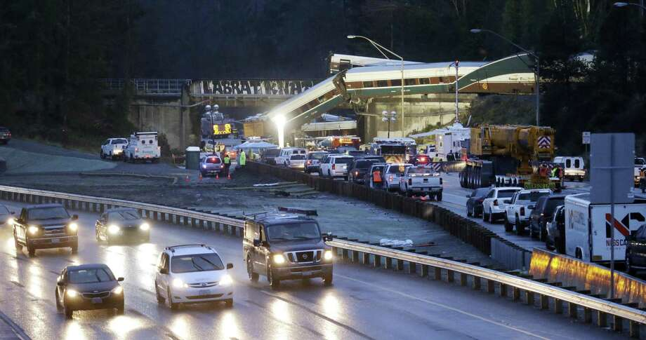 Traffic moves along northbound Interstate 5, left, as southbound lanes are filled with emergency vehicles near the scene of an Amtrak train crash Monday, Dec. 18, 2017, in DuPont, Wash. The Amtrak train making the first-ever run along a faster new route hurtled off the overpass Monday near Tacoma and spilled some of its cars onto the highway below, killing some people, authorities said. (AP Photo/Elaine Thompson) Photo: Elaine Thompson / Associated Press / Copyright 2017 The Associated Press. All rights reserved.