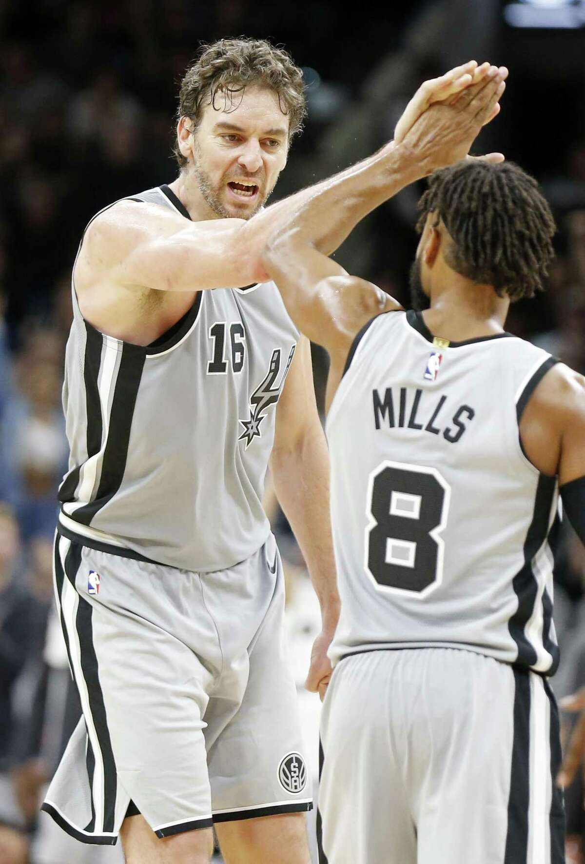 San Antonio Spurs' Pau Gasol celebrates with teammate Patty Mills after scoring a 3-pointer and being fouled during second half action against the Dallas Mavericks Monday Nov. 27, 2017 at the AT&T Center. The Spurs won 115-108.