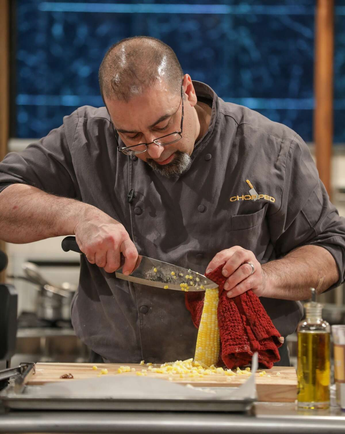 """Stephen Costanzo, co-owner and head chef at Olio in Stamford prepares polenta on an episode of Food Network's """"Chopped"""" that aired on Dec. 7, 2017. Costanzo won the competition."""